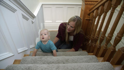 Mother and her infant son playing on the stairs Footage