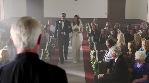 Father walking bride to the preacher at the front of a chapel Footage