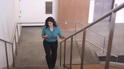 Panning wide shot of woman walking up stairs looking at smartphone Footage
