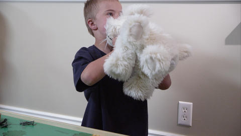 Boy picking up and throwing a white stuffed animal Footage
