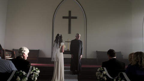 Shot of a bride standing without a groom in front of a preacher in a chapel Footage