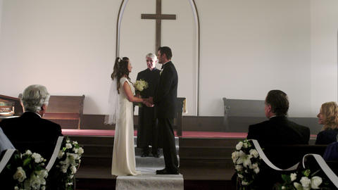 Bride and groom smiling as a preacher talks to them in the chapel Footage