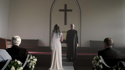 Bride standing without a groom in front of a preacher in a chapel Footage