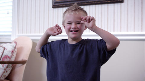 Medium shot of a downs boy clapping Footage