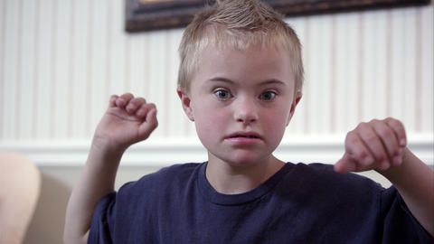 Medium shot of Downs Syndrome boy in a blue shirt Footage
