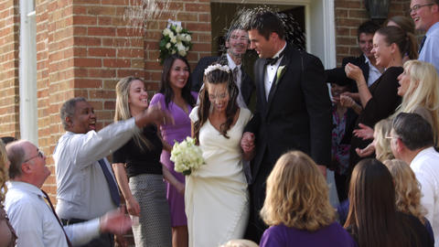 Slow-motion newlywed couple under thrown rice Footage