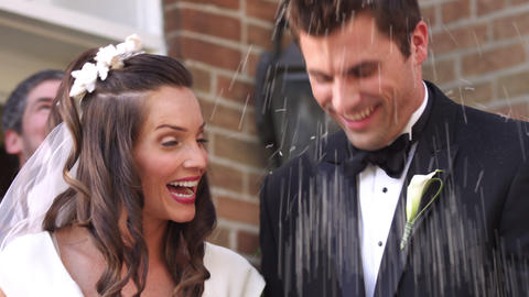 Slow-motion bride and groom under thrown rice Footage