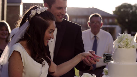 Newlywed couple cutting their wedding cake holding hands Footage