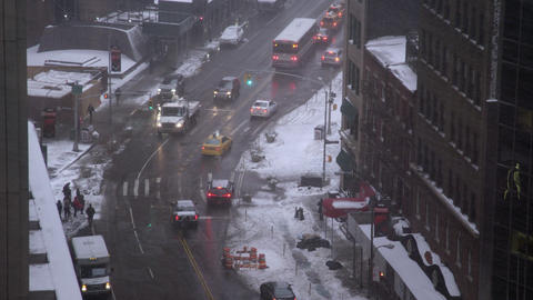 Slow motion zoom from building looking down to traffic while it is snowing Footage