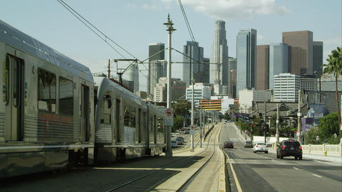 Slow panning shot of train driving down the street in Los Angeles Live Action