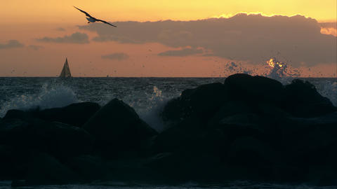 Slow motion view of a sailboat on the horizon while waves crash on the rocks Live Action