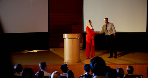 Multi-ethnic business people shaking hand on stage in business seminar at auditorium 4k Live Action