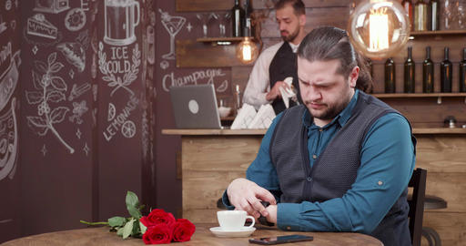 Handsome man with long hair waiting for his date in a... Stock Video Footage