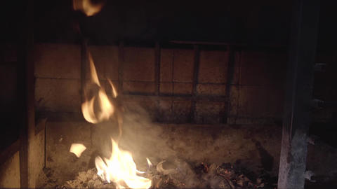 Fire burning in stone fireplace indoors. Close up view, slow motion Footage