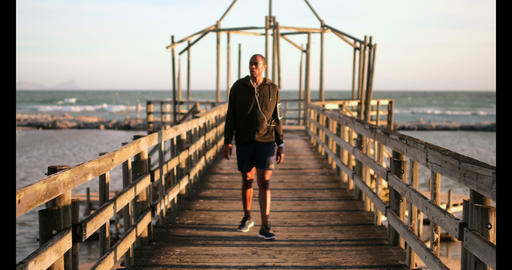 African American male jogger walking on pier at beach in the sunshine 4k Live Action