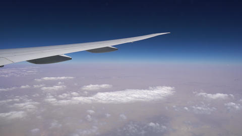 Plane wing over the horizon Blue sky high above the clouds, view from the plane Footage