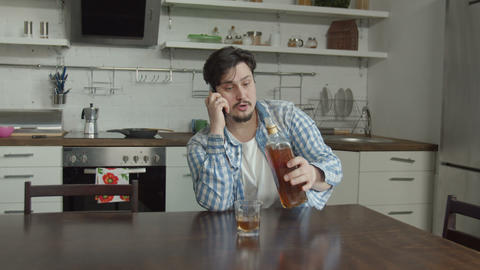 Man sitting in kitchen with bottle of alcohol Live Action