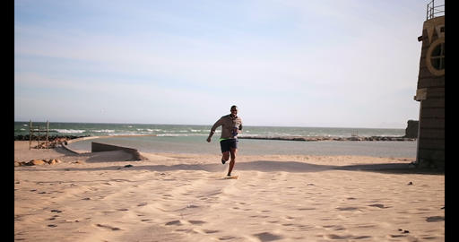 African American male runner jogging on beach in the sunshine 4k Live Action