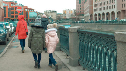 Girls with moms walking on city embankment on urban architecture background Footage