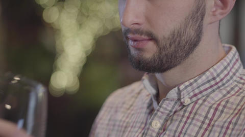 Close-up portrait of half face of bearded guy drinking wine and smoking hookah Live Action