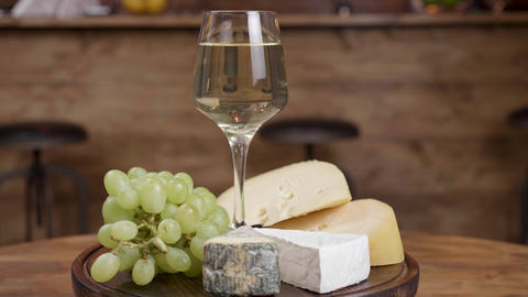 Beautiful rotation of a glass of wine with a variety of cheeses on a round ライブ動画