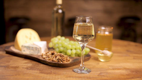 A glass of white wine on a wooden table served with cheese and grapes ライブ動画
