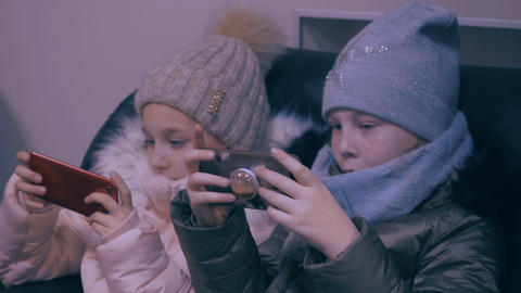 Two teenager girls in winter clothes watching mobile phones and playing in game Archivo