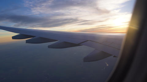 the wing of the aircraft in the setting sun. air travel, travel to other Live Action