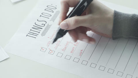 Female hand putting mark on check boxes of to do list Live Action