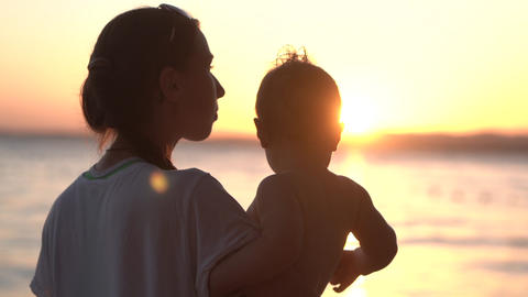 Mother shows beauty of life to her little baby at sunset in slow motion Footage