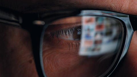 Man in glasses looking on the monitor and surfing Internet. The monitor screen Footage