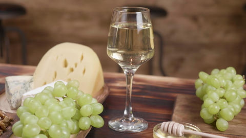 Rotating composition of cheese served with a glass of wine and grapes ライブ動画