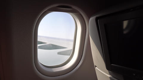 the wing of the aircraft in the window. window with seats on the plane. the Footage