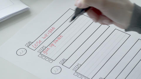 Woman writing steps with red marker on goal list Footage