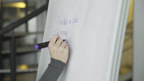 Close up of business woman hand writing business plan on flipchart Footage