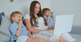 Young beautiful mother and two young children sitting on the couch looking at Footage