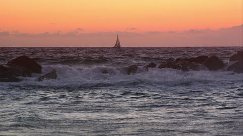 Slow motion view of sailboat on the horizon at sunset Live Action