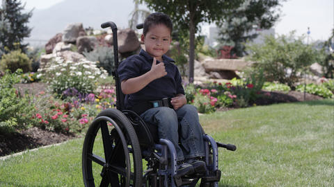 Little Latino boy sitting in a wheelchair in front of a rock and flower garden Live Action