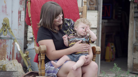 Woman holding child in lap while rocking in a rocking chair Live Action