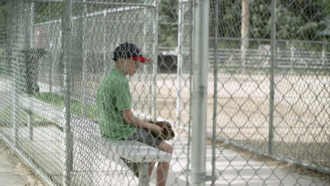 Slow motion push of boy sitting in dugout behind chain link fence Footage