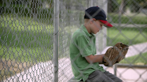 Slow motion rack focus of boy sitting behind chain link hitting baseball mitt Footage