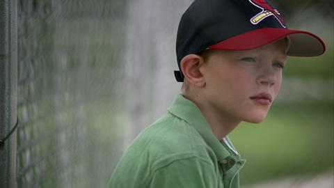 Slow motion pan of boy in baseball hat looking up Footage