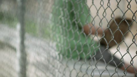 Slow motion rack focus of boy sitting in dugout behind chain link fence Footage
