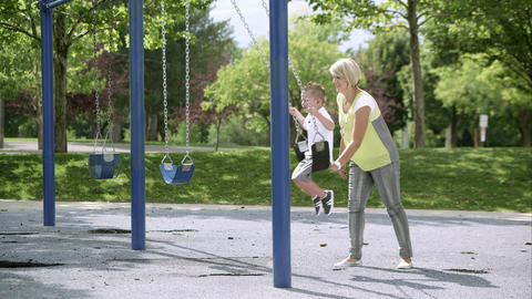 Slow motion of mother pushing young son in swing Live Action