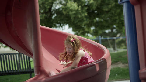 Slow motion of red headed girl coming down slide and smiling ビデオ