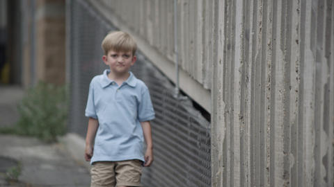 Slow motion of young boy walking in alley way with a fierce look on his face Footage