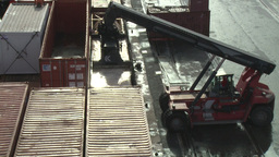 Forklift tractor moving metal shipping containers in harborForklift tractor movi Footage