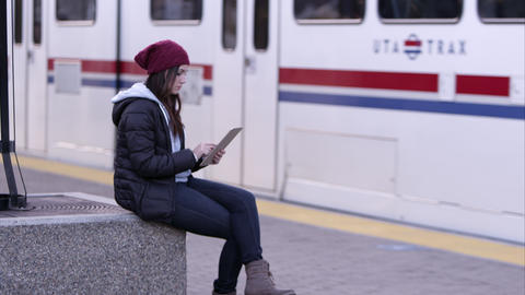Woman using tablet as transit train pulls to a stop Live Action
