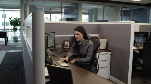 Panning view of woman in cubicle working on computer Footage