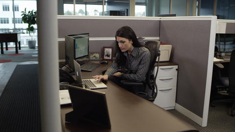 Woman in cubicle working on computer and looking at laptop Footage